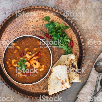 Prawn curry shrimp masala garnished with cilantro, served with naan bread on vintage copper tray. Top view, blank space