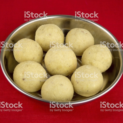 Indian laddoo (laddu) sweets served on silver plate sitting on a red tablecloth.